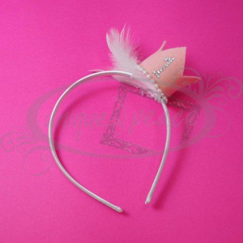 Χειροποίητη στέκα με στόλισμα κορώνα σε ροζ απαλό χρώμα και αριθμό(1-9 από στοιχεία swarovski της επιλογής σας), λευκή τρέσσα πέρλα και λευκό πούπουλο. Ιδανική για περίπτωση γενεθλίων.