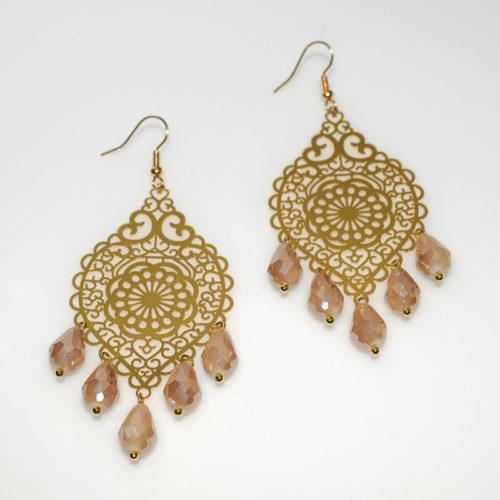 Χειροποίητα σκουλαρίκια από μεταλλικό σκαλιστό στοιχείο σε χρυσό/ροζ χρυσό χρώμα και σταγόνες σε λευκό/μπεζ χρώμα. Τα κουμπώματα είναι υποαλλεργικά σε σχήμα γάντζου.